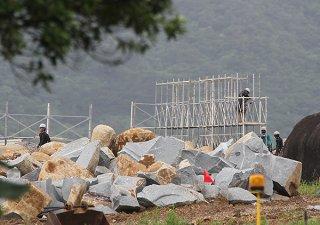 工事再開を受け、集められた岩石の回りに足場を設置する作業員ら=10日午後、石垣市平得大俣
