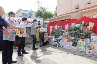 石垣島産パイン・マンゴーのゆうパック出荷が始まり、関係者が伝達して車両に積み込む=24日午前、八重山郵便局駐車場