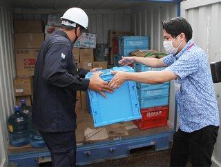 竹富島、小浜島にもエリア拡大したネットスーパー。店舗関係者らがボックスをコンテナに収納した=2日午前、八重山観光フェリー貨物専用事務所前