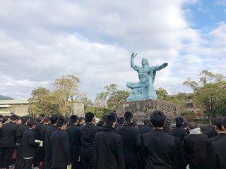昨年の修学旅行で長崎県の平和公園を訪れる石垣第二中学校の生徒ら=(同校提供)