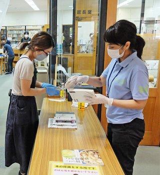 新型コロナウイルス感染防止対策として、返却された図書を消毒する職員。再開後も継続される=5月19日、市立図書館
