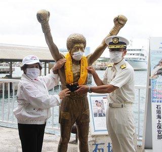 具志堅用高像にライフジャケットを付ける右から増田部長と辻野支部長=16日午前、石垣港離島ターミナル