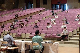 石垣市の新型コロナウイルス感染症対策について説明を受ける出席者ら=20日午後、市民会館大ホール