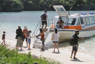 川平湾で手指消毒をしてグラスボートに乗り込む観光客ら=23日午後、川平