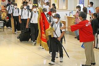 今大会特別に用意された深紅の優勝旗を手に凱旋する内間敬太郎主将と部員ら=3日午後、南ぬ島石垣空港