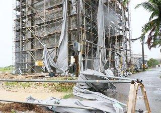 建設中の建物のシートが強風ではがれ、付近の電柱やフェンスに絡まった=3日午前、石垣市真栄里