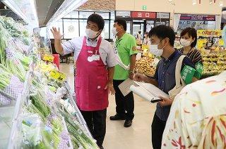 商品陳列棚で温度管理や消費期限の適正表示などをチェックする監視員ら(右側)=5日午前、マックスバリュやいま店