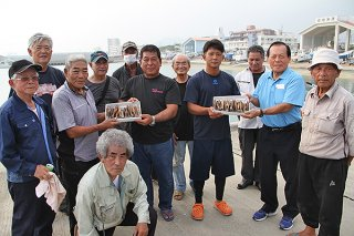 会員からエギ贈呈を受けた新入会員の浜さん(中央左)、川満さん(同右)=5日午後、石垣漁港