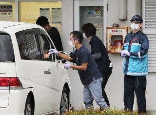 唾液採取用の容器を渡す医師=10日午前、中野わいわいホール駐車場