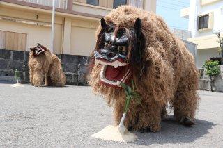 登野城村に見立てたアラスクヤ4隅の盛砂にススキのサンを挿し邪悪払いする2頭の獅子=3日午前、アラスクヤ