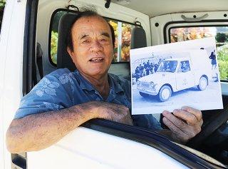 61年前と同じポーズをとる友利さん。写真には島内初となる自動車ダイハツ・ハイゼットと若かりし友利さんが写る=15日午後、竹富