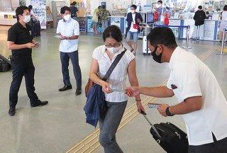 八重山青年会議所のメンバーが観光客らにポストカードを配布した=18日午後、ユーグレナ石垣港離島ターミナル
