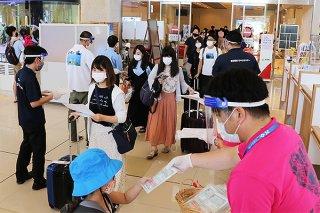 観光客にマスクや感染予防策のチラシを配る市観光交流協会=19日午後、新石垣空港