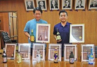 受賞ボトルと賞状を手にする座喜味代表取締役(右)=2日午後、市役所庁議室