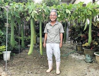 自宅の庭で実った大きなヘチマを前に笑顔を見せる崎山用照さん=9月21日、西表島祖納