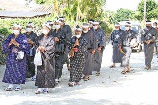76年ぶりに昼間に世乞い歌を歌いながら根原家へ向かう公民館役員や村の顧問ら=14日午前、竹富島