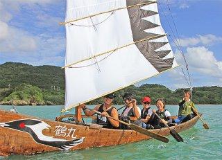 帆掛けサバニ「鶴丸」をこぐ参加者たち。帆は(同ユニオンが)小さくても大空を羽ばたけるようにとの願いが込められている=25日午後、明石橋海岸