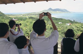玉取崎展望台で眺望を満喫する修学旅行生たち=27日午後、同所
