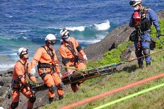 崖の下から負傷者を運ぶ消防隊員ら=29日、崎枝御神埼灯台周辺