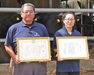 賞状を手に笑顔の上江洲さん(左)と嶺岸さん=10月31日午前、農業生産法人㈲ヤイマ・ブリーダー・ランチ牛舎前