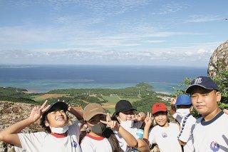 修学旅行の一環として野底マーペーを登り、笑顔を見せる宮良小学校の児童ら=10月29日、野底マーペー頂上