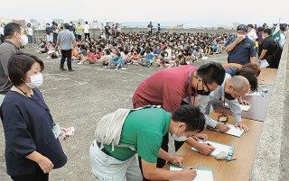 一時避難先に到着し、名簿に記入する市職員ら=5日午前、石垣小学校屋上