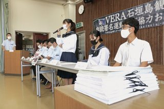 石垣市で集まった5099筆の署名(手前)。青木宙帆さんがVERAの運用継続を訴える=22日午後、市商工会ホール