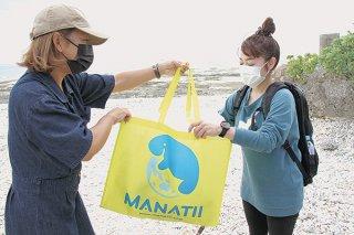 ビーチクリーン後、ごみの入ったレンタルバッグをパートナーへ返す参加者=28日午前、多田浜海岸