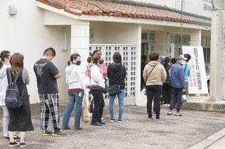 購入引換書を受け取ろうと会場入り口から100人以上が長蛇の列をつくった=22日午前、市中央運動公園