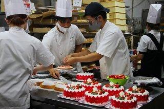 クリスマスに向けてデコレーションケーキの飾りつけを行うスタッフ=24日午前、メームイ製菓本店