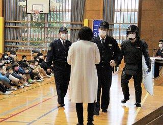 寸劇を通して正しい110番のやり方を伝える八重山警察署の警察官ら=8日午前、石垣小学校