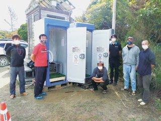 仮設型のバイオトイレを2基設置。事業を運営する関係者ら=20日午後、西表島マーレー駐車場