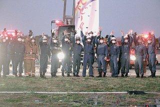 八重山病院へ向かって手を振る市消防本部職員ら=25日夕、石垣市消防本部