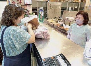 公設市場で旧正月用の豚肉などを買う女性(右)=11日午後