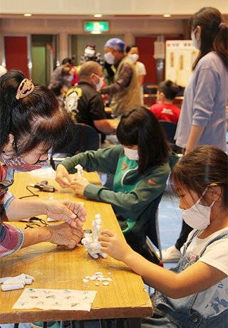 石垣市生涯学習フェスティバルと学び遊び体験広場が同時開催され、物作り体験に多くの親子連れが参加した=14日午前、市民会館中ホール