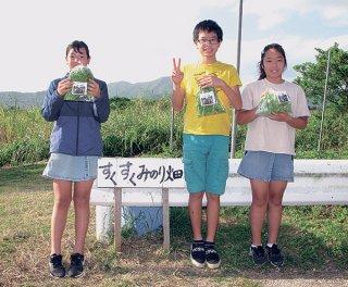 初めての無人販売に挑戦した畠山愛深さん、川満逞睦君、添盛結愛さん(右から)=16日午後、同校すくすくみのり畑