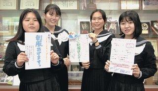 自作の「制服リレー」周知ポスターを掲げる家庭クラブの生徒たち=2月28日日午後、八重山高校小会議室