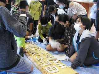 自分たちでデザインした文字や図柄の看板をサンゴ礫を貼り付けて作る児童ら=5日午後、八島小学校体育館