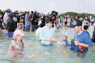 初泳ぎで果物を集める子どもたち。八重山から一足早い夏の到来を全国にアピールした=20日午前、竹富島コンドイ浜