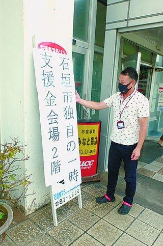 6日の一時支援金センター開設に向け、看板の設置場所を確認する市商工会職員=5日午後、石垣港ターミナル