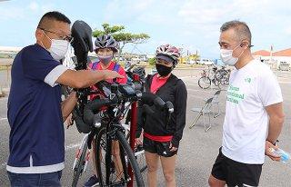 石垣島トライアスロン大会を前にバイクのメンテナンスを受ける出場者ら=10日午前、八島町