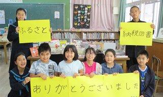 ふるさと納税図書に謝意を表す川平小中の児童生徒(同校提供)
