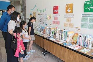 企画展を訪れ、本を見てまわる家族連れ=18日午後、石垣市立図書館