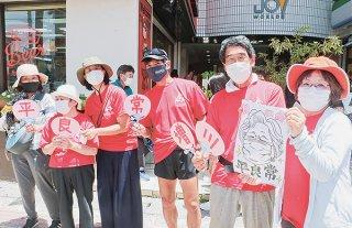 伴ネットやいまのメンバーが同会会長を長年務めた平良常さんを応援した=1日午後、730交差点付近