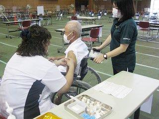 高齢者を対象とした新型コロナウイルスワクチン接種を受ける人=17日午後、市総合体育館メインアリーナ
