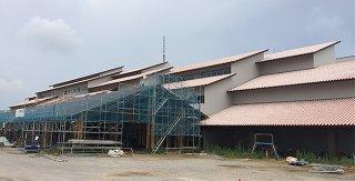 寄付者名前入りの赤瓦が乗せられる正面玄関前の屋根(足場が組まれている部分)=8日午後
