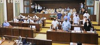 自治基本条例改正案に起立して賛成する与党10氏=28日午後、本会議場