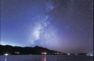 石垣島の北部で撮影した夜空。山の向こうから市街地の明かりが空を照らす(市観光交流協会提供)