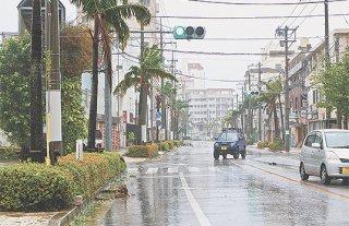 台風の接近に伴い暴風が吹き荒れた市街地。街路樹が折れたり停電で止まる信号があった=23日午後、市役所前
