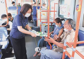 乗客にチラシを配布し適切な西表島観光の在り方を周知する=28日午前、南ぬ島石垣空港